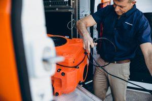 water damage restoration technician taking equipment out of van
