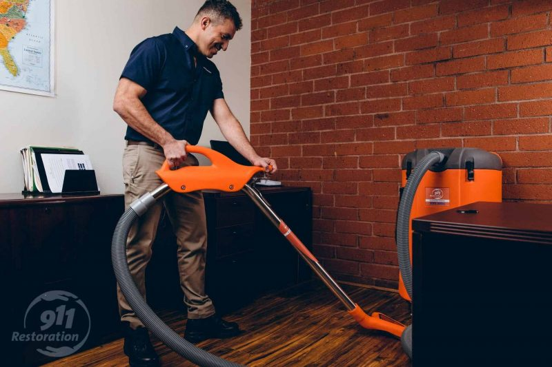 commercial restoration technician vacuuming water in office